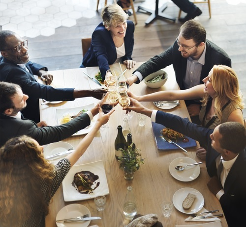 Business people in a restaurant raising glasses to toast
